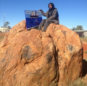 Artist Vincent Namatjira with his painting The First Exploration and Settlers to Australia. Photo by Katie Spain